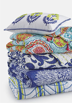 A stack of folded quilts in a variety of colors & patterns. Quilts. Shop now.