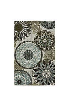 A rug with a medalion print in a variety of green hues. Shop rugs.
