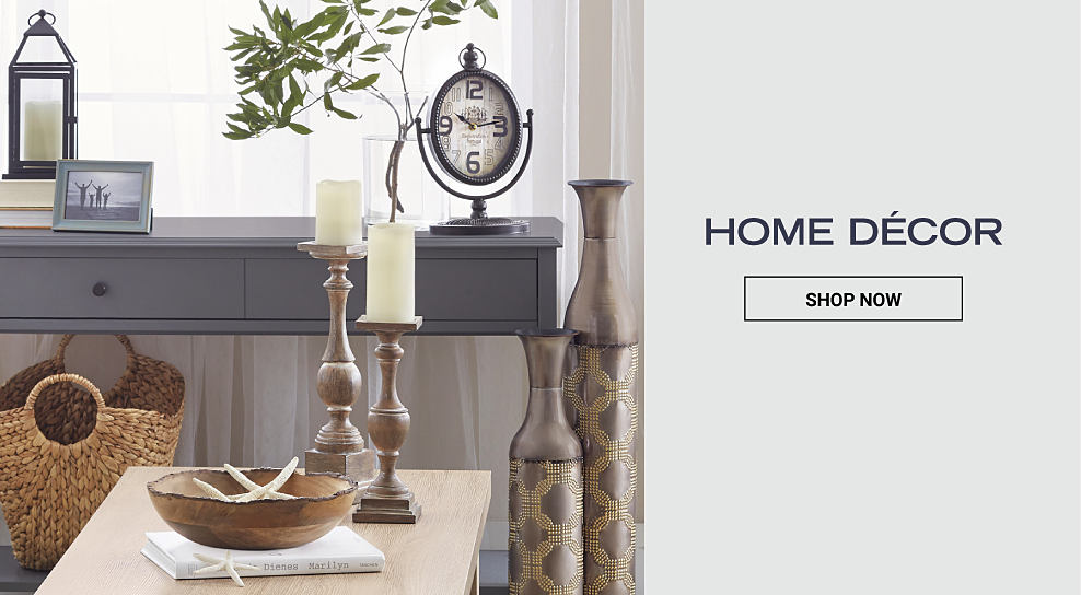 A living room decorated with a variety of decor including a whicker basket, a decorative bowl, candles and more. Shop Home Decor.