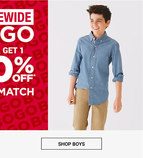 A boy wearing a chambray button up with long sleeves and khaki pants. Storewide Buy 1, Get 1 50% off. Mix and match. Shop boys.