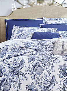 A bed with a white comforter with navy print and pillows to match. Bedding collections. Shop now.