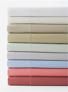 A stack of folded sheets in a variety of colors. Sheets. Shop now.