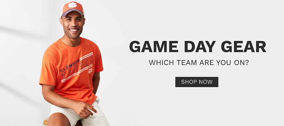 A young man wearing an orange, blue & white Clemson Tigers baseball cap, an orange, blue & white Clemson Tigers T shirt & white shorts. Game Day Gear. Which team are you on? Shop now.