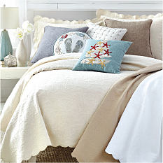 A bed made with an off white quilt & an assortment of throw pillows in a variety of colors & styles. Quilts. Shop now.