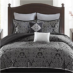 A bed made with a black & gray patterned comforter & matching pillows. Bed in a bag. Shop now.