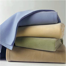A stack of folded blankets in a vauiety of colors. Blankets. Shop now.