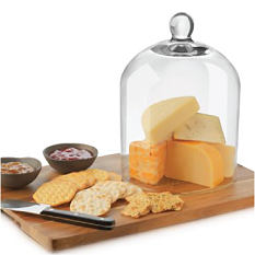 A wood cutting board with cheese knife, cheese, crackers & glass dome covering the cheese. Serveware. Shop now.