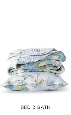 A folded multi-colored blanket on top of a matching pillow. Shop bed & bath.