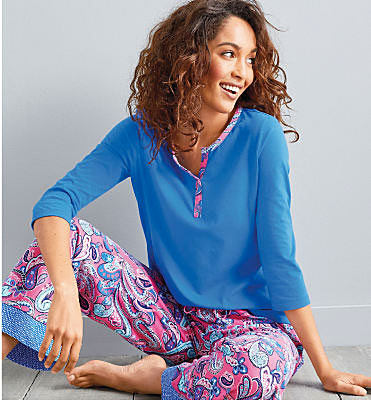 woman sitting in a blue top and floral pant