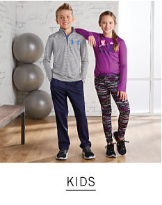Two kids standing in a gym. Shop kids.