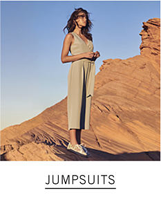 A woman wearing a beige sleeveless jumpsuit & flats. Shop jumpsuits.