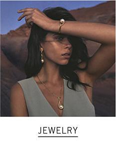 A woman wearing a gray sleeveless top, a bracelet, earrings & a necklace. Shop jewelry.