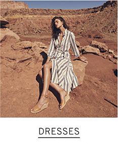 A woman wearing a beige & white vertical striped long sleeved dress. Shop dresses