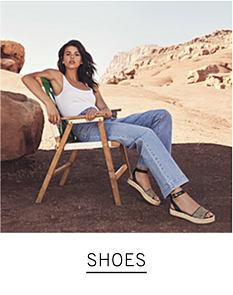 A woman wearing a white tank top, jeans & sandals. Shop shoes.