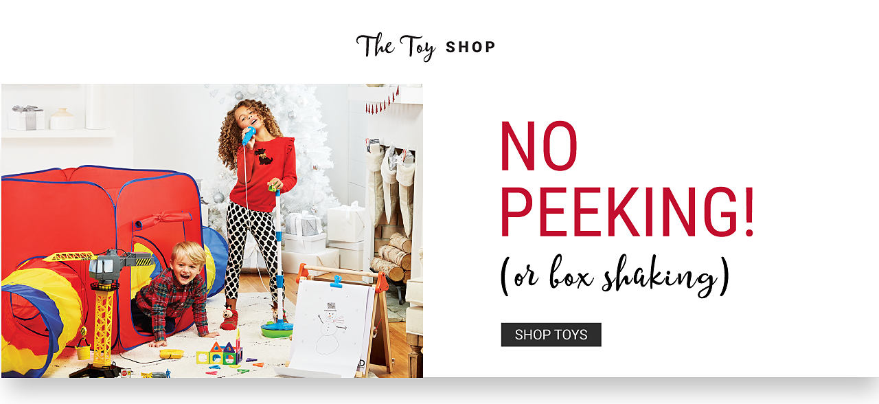 A boy sitting in a red, blue & yellow play house. A girl playing with a toy microphone. There's an easel & a toy construction set next to them. The Toy Shop. No Peeking or Box Shaking. Shop toys.
