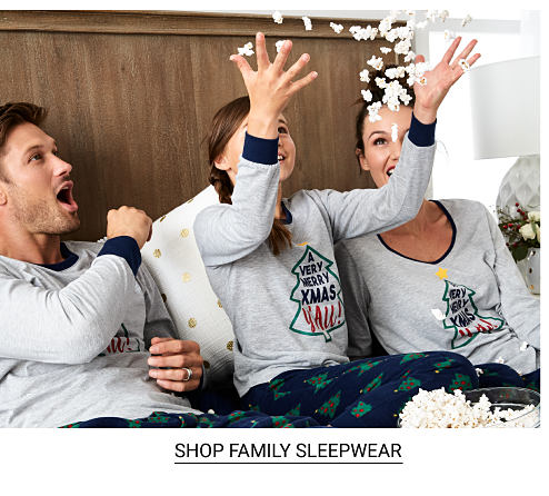 A father, mother and girl sitting in a bed wearing matching gray pajamas with a multi colored Christmas tree front graphic. Shop family sleepwear.
