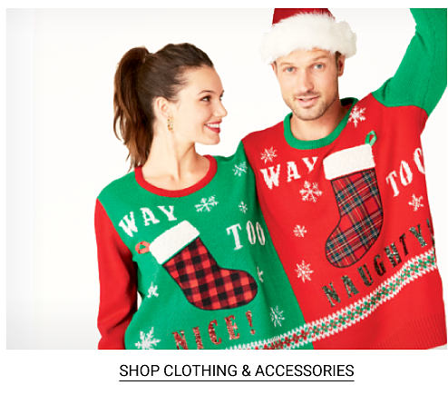 A woman wearing a green, red, black & white Way Too Nice sweater with a Christmas stocking front graphic standing next to a man wearing a Santa hat & a a green, red, black & white Way Too Naughty sweater with a Christmas stocking front graphic. Shop ugly sweaters