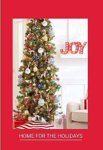 A fully decorated Christmas tree next to a white couch. Shop Home for the Holidays.