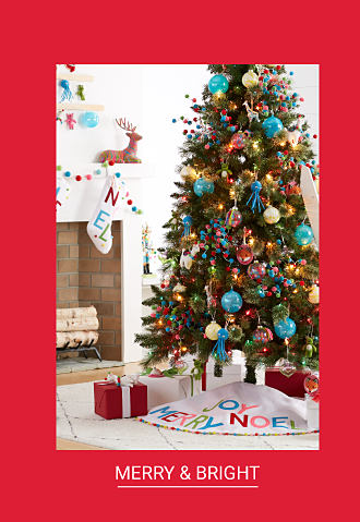 A fully decorated Christmas tree next to a fireplace. Shop Merry & Bright.