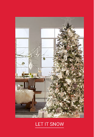 A fully decorated Christmas tree next to a window. Shop Let It Snow.