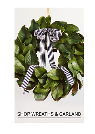 A green Christmas wreath with gray ribbons. Shop wreaths and garland.