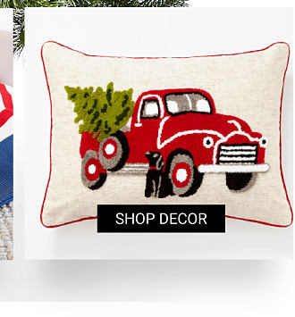 A pillow with a red pickup truck carrying a Christmas tree embroiedery. Shop decor