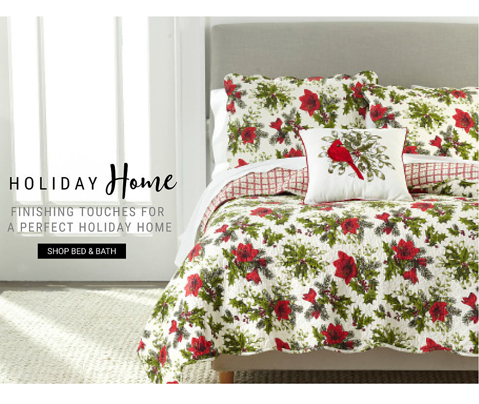 A bed made with a red, white & green poinsettia patterned print comforter and pillows. Holiday Home. Finishing touches for a perfect holiday home.