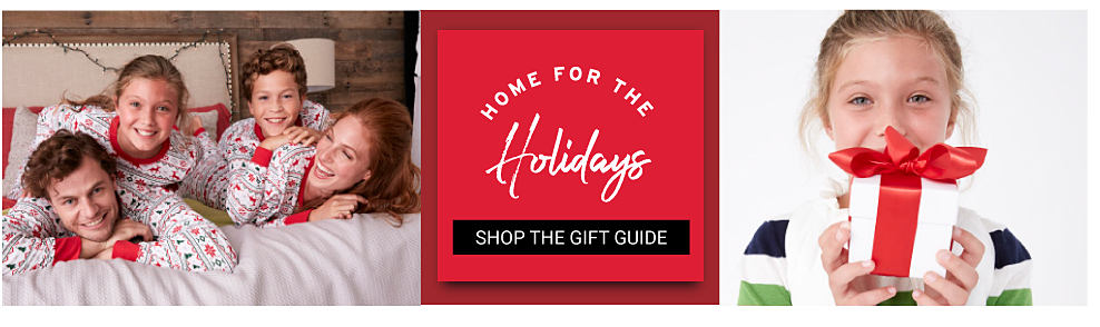 A father, mother, boy & girl all wearing matching white, red & green patterned print pajamas lying on a bed. A girl wearing a green, blue & white horizontal striped shirt holding a white box with a red ribbon. Home for the Holidays. Shop the Gift Guide.