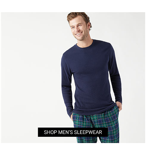 A man wearing a gray long sleeved henley shirt & red, black & white plaid lounge pants