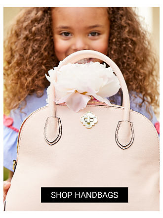 A girl standing behind a peach leather handbag with a white flower perched on top. Shop handbags.