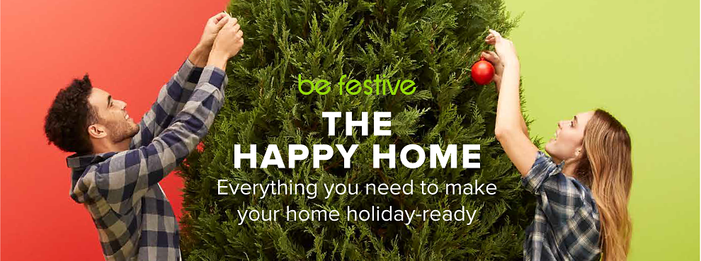 A man and a woman in plaid shirts hanging Christmas ornaments on a tall tree. Be festive. The happy home. Everything you need to make your home holiday ready.