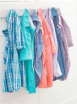 An assortment of men's short-sleeved button front shirts in a variety of colors & styles hanging from hooks on a wall. Shirts. Shop now.