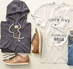 A folded gray hoodie, a black & white Let's Throw Down graphic T-shirt, a folded pair of blue jeans & a pair of brown leather shoes. Shop True Craft.