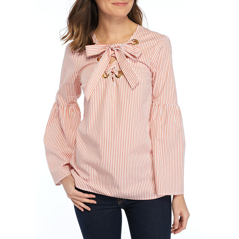 A woman wearing a beige long sleeved top with bow neckline detail & black pants. Shop women.