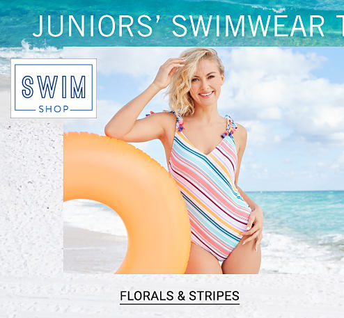 Swim Shop. Juniors Swimwear Trends. A young woman wearing a multi colored diagonal striped one piece swimsuit. Shop florals & stripes.