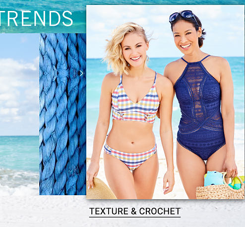 A young woman wearing a multi colored plaid bikini standing next to a woman wearing a blue crochet one piece swimsuit. Shop texture & crochet.