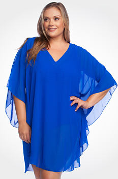 A young woman wearing a blue poncho style swim cover up. Shop cover ups.
