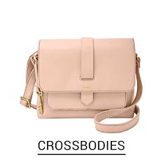 A pale pink crossbody bag. Shop Crossbodie.