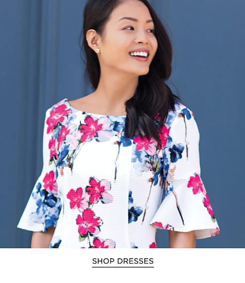 A woman wearing a short-sleeved white, fuchsia & blue floral print dress. Shop Dresses.