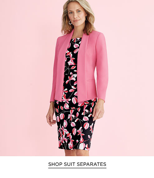 A woman wearing a knee length black dress with a pink floral print and a long-sleeved pink blazer. Shop suit separates.