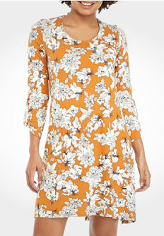 A young woman wearing a yellow & white floral print long sleeved dress. Shop dresses.