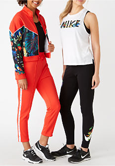 A young woman wearing a red track suit with a multi colored print on the jacket, a black T shirt & black sneakers standing next to a woman wearing a white sleeveless tee with a black Nike logo, black yoga pants & black sneakers. Shop activewear.