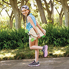 A girl wearing a multi-colored hat, a light blue sleeveless tee, white shorts & dark gray sneakers. Shop girls.