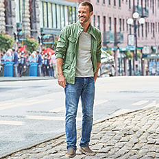A man wearing a green jacket, a white T-shirt, blue jeans & gray sneakers. Shop men.