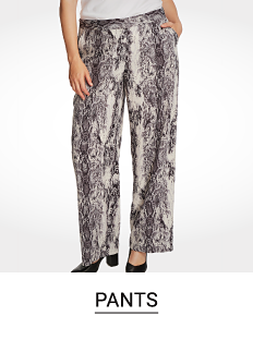 A woman in black and white printed flowy pants. Shop pants.