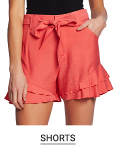A woman in coral colored shorts and a black top. Shop shorts.