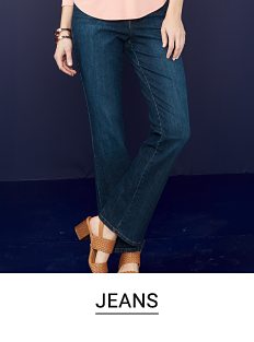 A woman in a red top, dark wash jeans and flats. Shop jeans.
