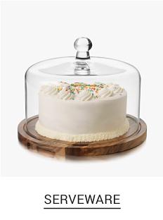 A white cake under a clear glass cake down. Shop serveware.
