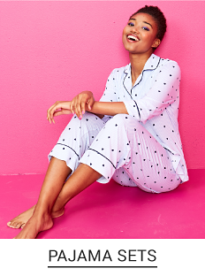 A young woman in a navy graphic tee, navy pants with colorful polka dots and a light pink long cardigan. Shop pajama sets.