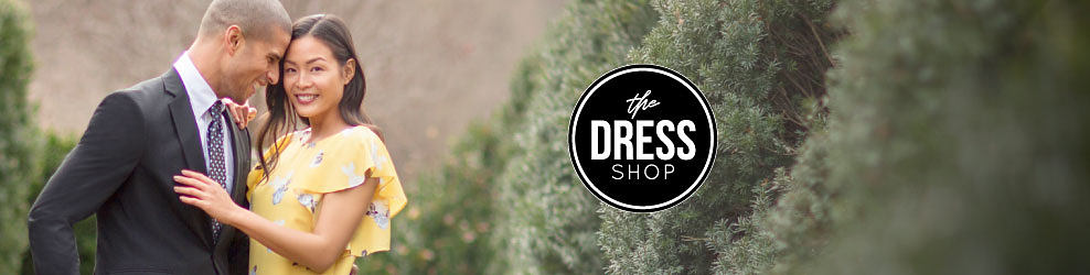 A man wearing a gray sport coat, a white dress shirt & a gray tie with white dots standing next to a woman wearing a yellow, white & blue print short sleeved dress. The Dress Shop. Dresses for Every Size. Shop Womens dresses. Shop Plus Dresses. Shop Petite Dresses.